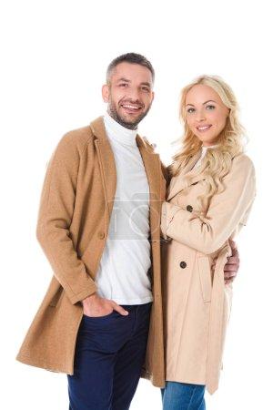 Photo pour Heureux couple belle posant dans des manteaux beiges, isolés sur blanc - image libre de droit