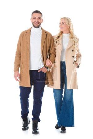 Photo pour Beau couple marchant dans les manteaux beiges, isolés sur blanc - image libre de droit