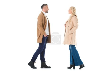 Photo for Smiling couple posing in trendy beige coats, isolated on white - Royalty Free Image