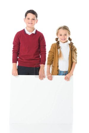 smiling siblings standing with empty board, isolated on white