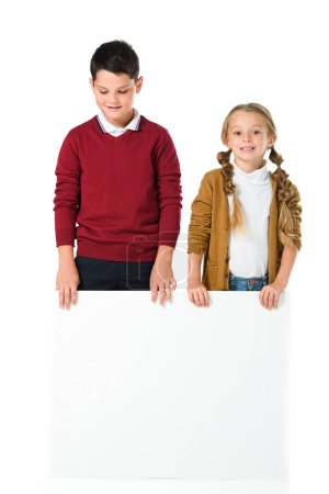 adorable siblings standing with blank placard, isolated on white