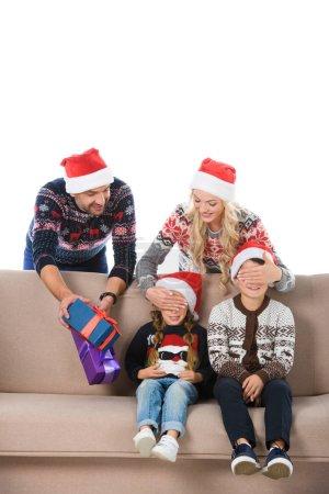 Photo pour Parents en chapeaux santa holding Noël présente, fermant les yeux et faire la surprise pour les enfants, isolés sur blanc - image libre de droit