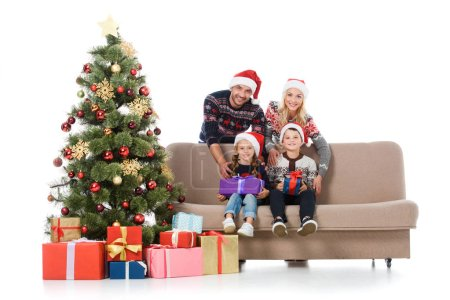 smiling family with kids in santa hats sitting on sofa near christmas tree with gift boxes, isolated on white