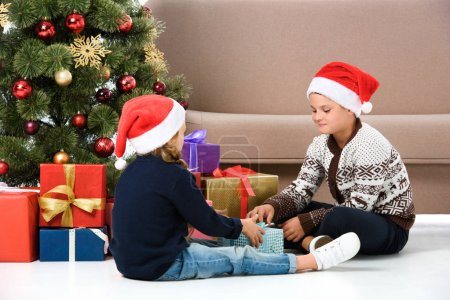 children in santa hat sitting near christmas tree with gifts