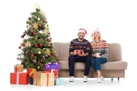 Photo for Happy couple with cups of coffee and sitting on sofa near christmas tree with presents, isolated on white - Royalty Free Image