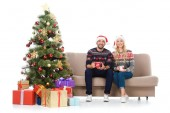 happy couple with cups of coffee and sitting on sofa near christmas tree with presents, isolated on white