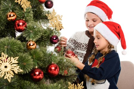 kids in santa hat decorating christmas tree with balls