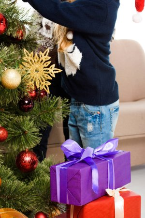 cropped view of kids near christmas tree with gift boxes