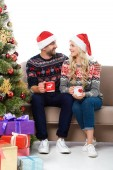 beautiful couple in santa hats holding cups of coffee and sitting on sofa near christmas tree with gifts, isolated on white