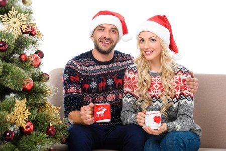 Photo pour Beau couple en chapeaux santa tenant des tasses de café et assis sur le canapé près d'arbre de Noël, isolé sur blanc - image libre de droit