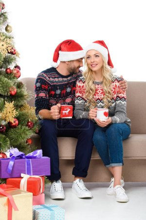 Photo for Beautiful couple in santa hats holding cups of coffee and sitting on sofa near christmas tree with gift boxes, isolated on white - Royalty Free Image