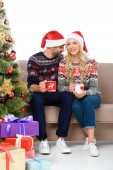beautiful couple in santa hats holding cups of coffee and sitting on sofa near christmas tree with gift boxes, isolated on white