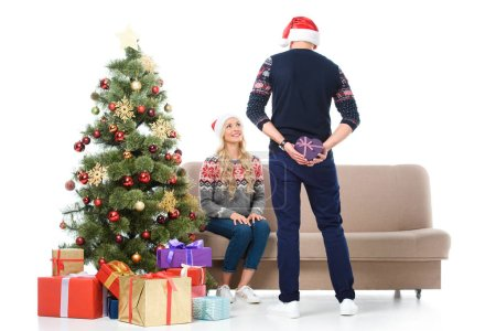 woman looking at man hiding heart shaped gift and standing near christmas tree, isolated on white