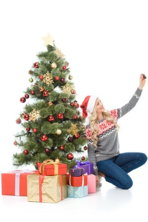 Photo pour Femme heureuse assis près d'arbre de Noël avec des cadeaux et prenant selfie sur smartphone, isolé sur blanc - image libre de droit
