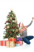 happy woman sitting near christmas tree with gifts and taking selfie on smartphone, isolated on white