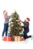 happy couple in santa hats decorating christmas tree with presents, isolated on white