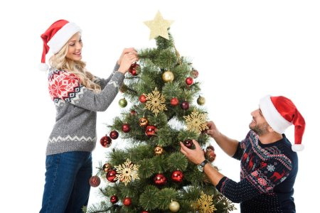 smiling couple in santa hats decorating christmas tree with balls, isolated on white