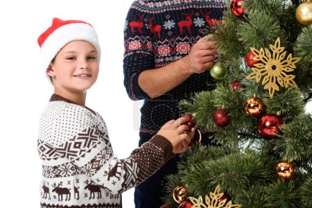 son in santa hat and father decorating christmas tree with balls, isolated on white