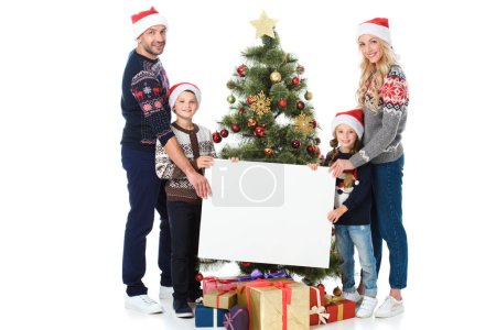 happy family holding empty board against christmas tree with parents, isolated on white