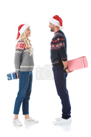 christmas couple in sweaters and santa hats hiding gift boxes, isolated on white
