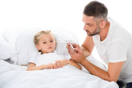 father looking at electronic thermometer while sick daughter with temperature lying in bed, isolated on white