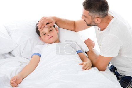 father touching forehead of sick son with temperature lying in bed, isolated on white