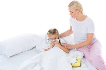 sick daughter blowing her runny nose in bed while mom sitting near, isolated on white