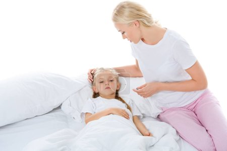Photo pour Mère avec thermomètre électronique regardant fille malade au lit, isolé sur blanc - image libre de droit