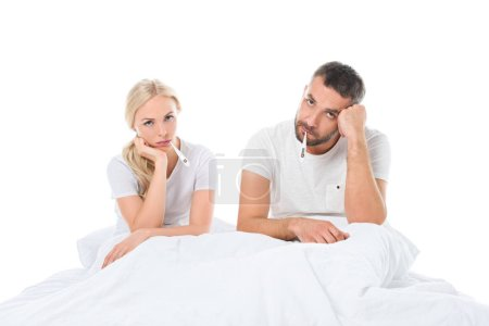 ill couple with electronic thermometers sitting in bed, isolated on white