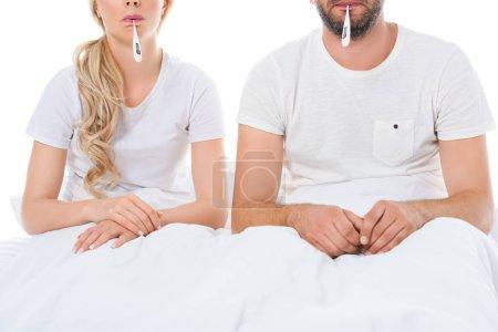 Photo pour Vue recadrée du couple malade avec des thermomètres électroniques, assis dans son lit, isolé sur blanc - image libre de droit