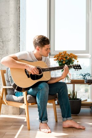 Photo for Young man in armchair playing acoustic guitar at home - Royalty Free Image
