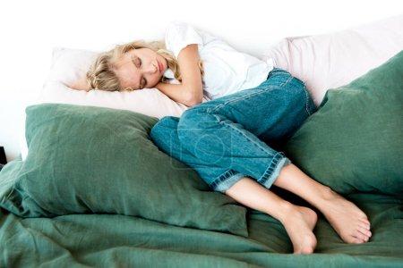 jeune femme en vêtements tout-aller dormir sur des oreillers sur le lit à la maison