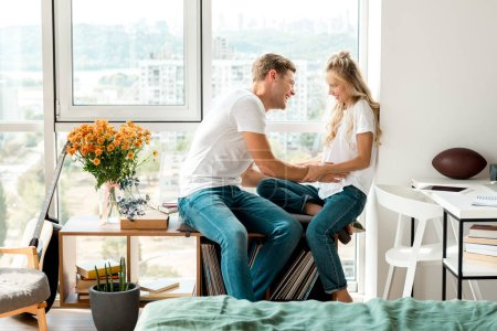 happy young couple in love sitting at window together at home
