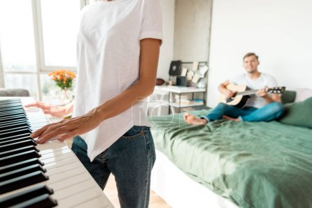 partial view of man playing acoustic guitar on bed while girlfriend playing electronic piano at home