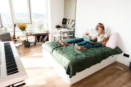 Photo for Happy couple with digital laptop resting on bed at home - Royalty Free Image
