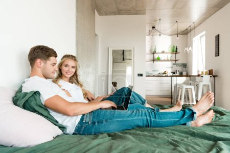 Photo for Smiling young couple with digital laptop resting on bed at home - Royalty Free Image
