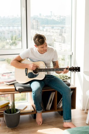 Photo pour Jeune mâle guitariste jouant de la guitare acoustique tout en étant assis à la fenêtre à la maison - image libre de droit