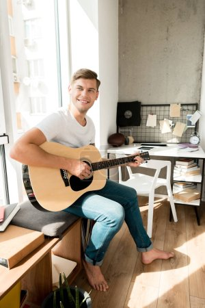 young smiling man playing acoustic guitar at home