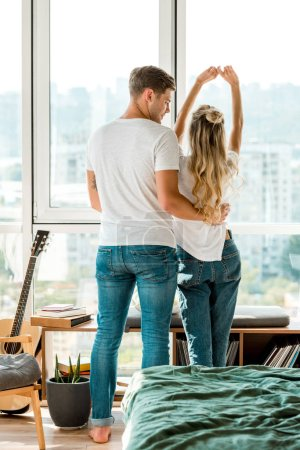 back view of young couple standing at window