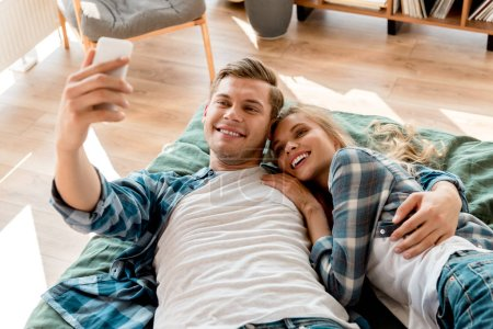 portrait of cheerful young couple taking selfie on smartphone while lying on bed at home