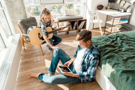 high angle view of man using digital tablet while girlfriend playing acoustic guitar at home