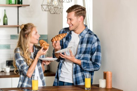 smiling couple eating croissants for breakfast in kitchen at home