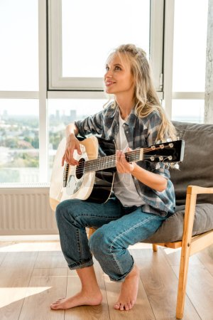 young beautiful female guitarist in casual clothing playing acoustic guitar at home