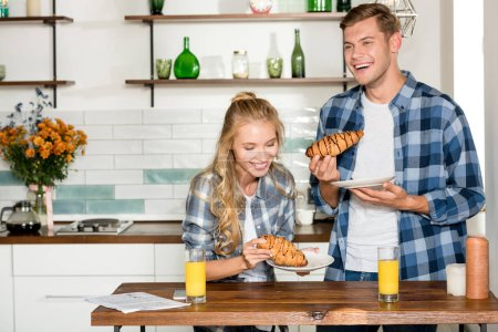 portrait of happy couple eating croissants for breakfast in kitchen at home