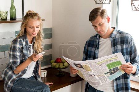 Photo pour Couple avec smartphone et journal passer la matinée dans la cuisine à la maison - image libre de droit