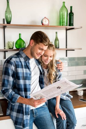 loving couple in casual clothing reading newspaper in kitchen at home