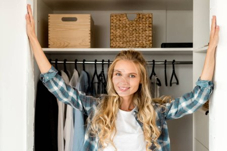 Photo for Portrait of smiling woman standing at wardrobe at home - Royalty Free Image