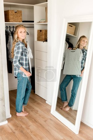 Photo for Young smiling woman fitting grey tshirt in front of mirror at home - Royalty Free Image