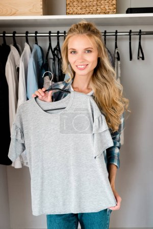 Photo for Young smiling woman fitting grey tshirt at home - Royalty Free Image