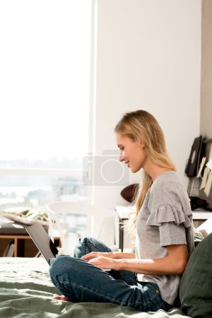 side view of beautiful woman using laptop while sitting on bed at home